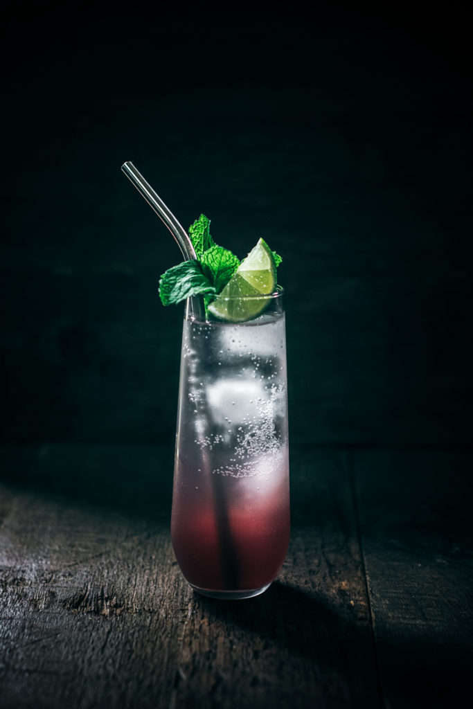 An ombre mojito with sangria and garnished with mint and lime